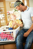 Father And Son Sorting Laundry. Sitting On Kitchen Counter Stock Photos