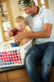 Father And Son Sorting Laundry. Sitting On Kitchen Counter Stock Image