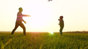 Father and son spend time together, launching and playing with the plane against the backdrop of a beautiful sunset. The