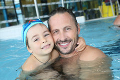 Father and son spending good time in pool. Portrait of men with cute little boy in swimming pool Stock Photos