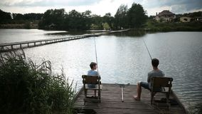 Father and son spending leisure fishing at pond stock video footage