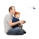 Father and son spending time playing together. Flying radio controlled helicopter.  On white Royalty Free Stock Image