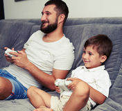 Father and son are spending time playing a videogame. Father and his small son are spending time playing a videogame together Royalty Free Stock Photography