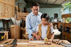 Father and son spending time together. Asian mature men explaining his son how to measure wood stock photos