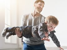 Father and son spending time together at home. Father and son spending time together. Dad is holding his son at home in living room stock photography