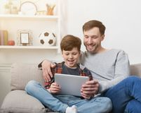 Father and son using tablet together on sofa at home stock photography