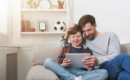 Father and son using tablet together on sofa at home stock photo