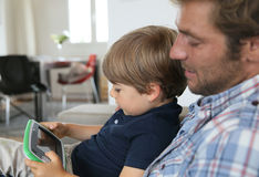 Father and son spending time together playing video game Royalty Free Stock Image