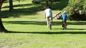 Father and son spending time together while riding bikes stock video footage