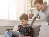 Father and son using tablet together on sofa at home royalty free stock photo
