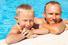 Father and son spent time in pool. Happy son swims with his father into the pool Royalty Free Stock Image