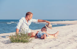 Father with son spent time together on the sea sand beach in sun Stock Photography
