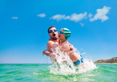 Father son splash water sea throw Royalty Free Stock Photography