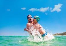 Father son splash water sea throw Royalty Free Stock Photography