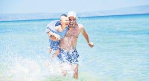 Father son splashes running sea Stock Photos