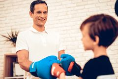 Man and Boy in Boxing Gloves Greet Each Other. Father and Son Spotting. Sport at Home. Warm Up in Quarter. Greet Each Other. Red and Blue Boxing Gloves. Doing stock photography