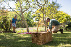Father and son spreading the picnic blanket. In the park Royalty Free Stock Photography