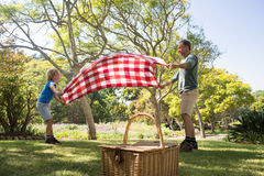 Father and son spreading the picnic blanket. In the park Stock Image