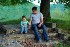 Father and son on stairs. family ties concept. Father and son sitting on stairs under an old tree. family ties concept Royalty Free Stock Image