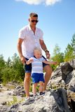Father and son stand on big stone Royalty Free Stock Photos