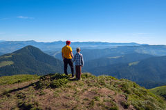 Father and son stand on peak and look into the distance. Wonderful adventure outdoor. Sunny wonderful day in the mountains. Back view royalty free stock photo