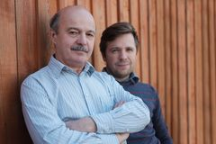 Father and son stand together near wooden background. Royalty Free Stock Photos
