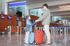 Father and son standing in airport hall Stock Images