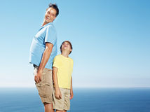 Father and son standing back to back Stock Photo