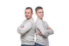 Father and son standing. Back to back. Studio shot isolated on white background. Copy space Stock Photo