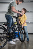 Father and son standing with bicycle and looking at each other Royalty Free Stock Photography