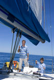 Father and son (8-10) standing at helm of sailing boat out to sea, boy steering, man holding rigging, smiling Stock Image