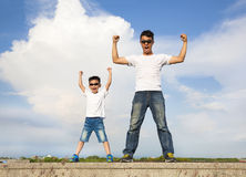 Father and son standing  and raising hands Royalty Free Stock Image