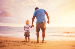 Father and son. Standing on the sea shore holding hands at sunset