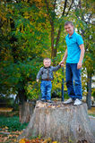 Father and son standing on a stump in the park Stock Photography
