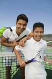 Father and son standing t on tennis court. Father and son standing at net on tennis court, portrait royalty free stock image
