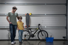 Father and son standing together in workshop with bicycle and skateboard Royalty Free Stock Image