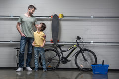 Father and son standing together in workshop with bicycle and skateboard Stock Image