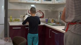 Father and son start cooking food. Dad sends her son a kitchen board. stock video footage