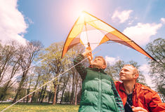 Father with son start to fly a kite Stock Images