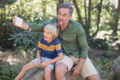 Father and son sticking out tongue while taking selfie in forest. Mischief father and son sticking out tongue while taking selfie in forest Stock Image