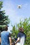 Father and son on summer day flying drone on countryside. royalty free stock photography