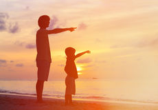 Father and son at sunset beach, pointing to the. Father and son at sunset beach, pointing at the sun Royalty Free Stock Images