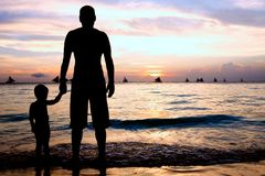 Father and son on sunset sea Stock Photo