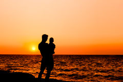 Father and son at sunset sea Stock Photography