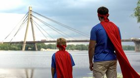 Father and son in superman costumes looking at bridge, dads support concept stock images