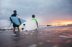 Father and son with surfboards preparing to surf at sunset Royalty Free Stock Photo