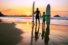 Father and son surfers meet a sunset on the ocean beach Stock Photo