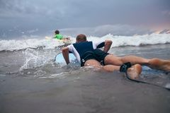 Father and son surfers overcome waves on surf line Stock Photo