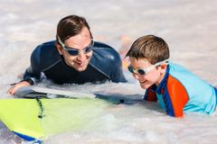 Father and son boogie boarding. Father and son surfing on boogie boards stock image