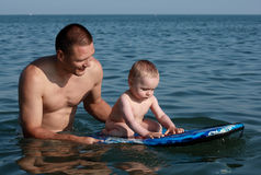 Father and son swimming. Boy sitting on a bodyboard  with his father pushing the board Stock Photo